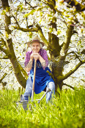 gardener sitting spade watering can tree