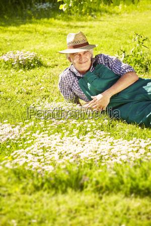 gardener lying on meadow flowers mouth