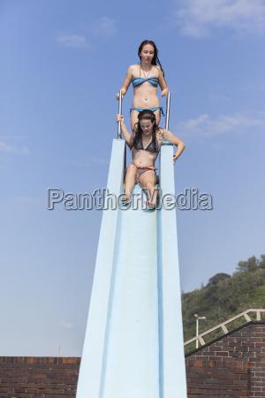 girl swimming pool slide fun
