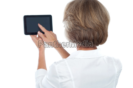 mature woman using tablet from back