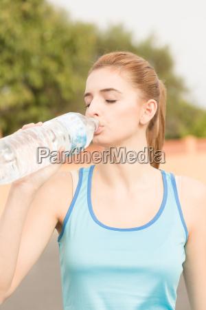junge frau macht sport und trinkt