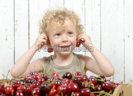 ein kleiner blonder junge isst kirschen