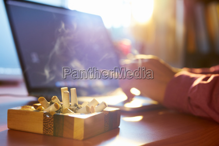 man using laptop and smoking cigarette