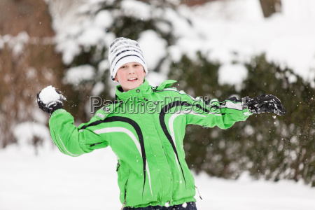 young boy throwing snowballs
