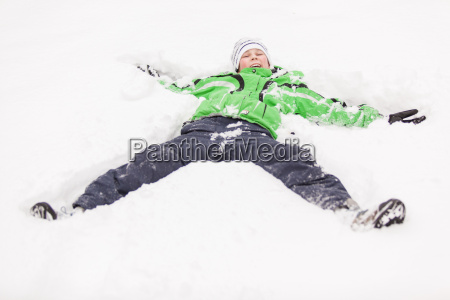 young boy playing in snow lying