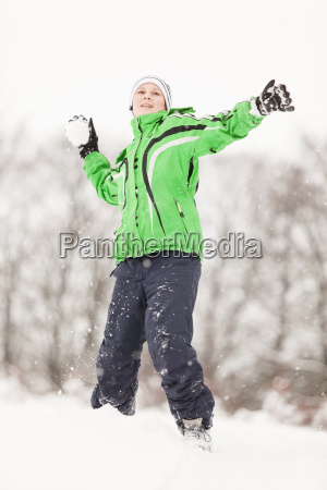 happy young boy having a snowball