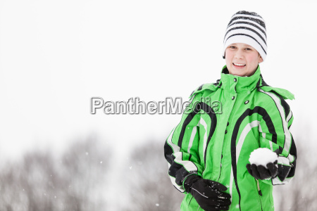 young boy displaying a snowball