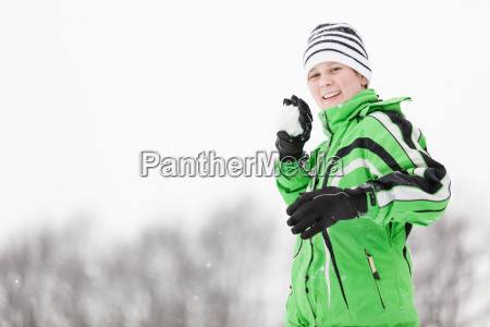 playful young boy taking aim with