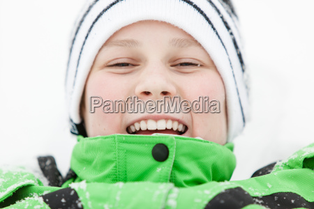 happy laughing boy lying in winter