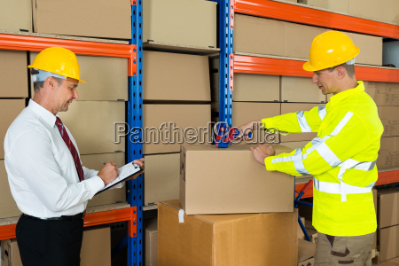 manager with clipboard and worker taping
