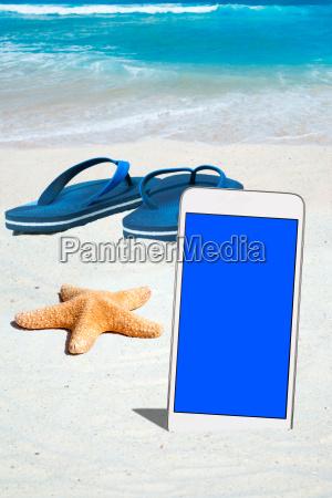 smartphone flip flops and starfish on