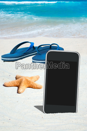 smartphone flip flops and starfish on