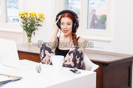 junge frau hoert musik am computer