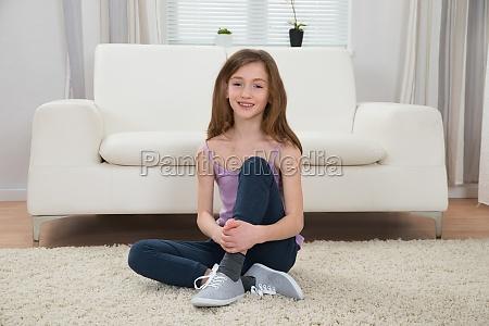 girl sitting on carpet in living