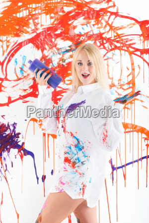 brightly painted woman presenting finger paints