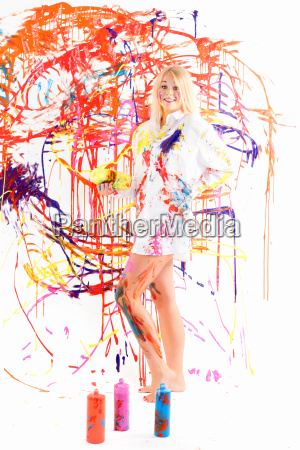 blonde painting a wall of colorful