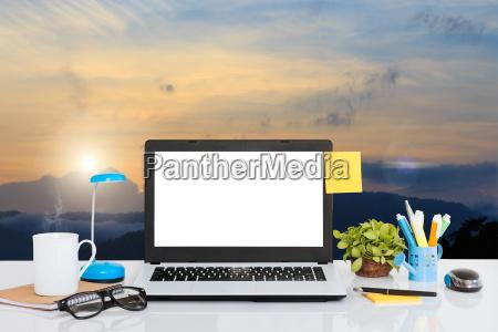 laptop computer on desk and landscape