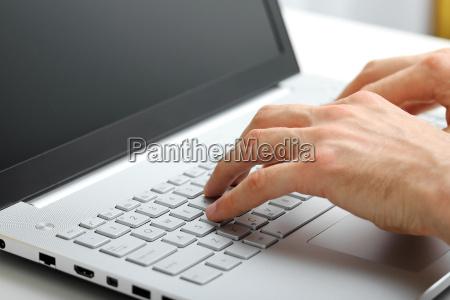 haende tippen auf laptop tastatur