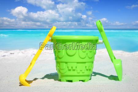 buntes strandspielzeug steht im sand am