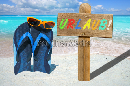 flip flops sunglasses and wooden sign
