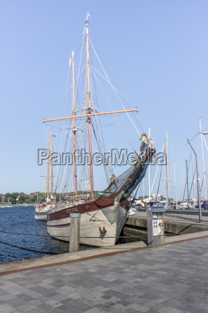 wooden sailboat moored in the harbor