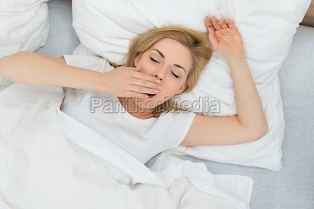 gaehnende frau im schlafzimmer