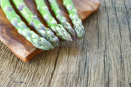 gruene spargelstangen auf schneidebrett mit textfreiraum