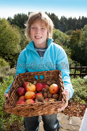 young boy posing with a basket