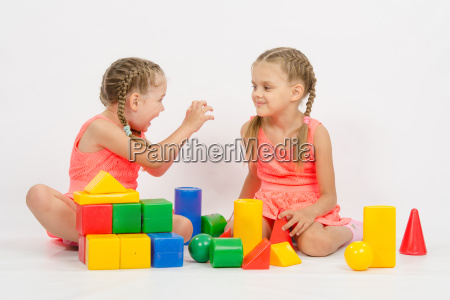 girl frighten another girl playing with