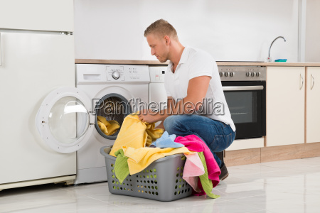 man putting dirty clothes into the