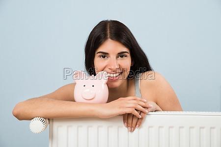 woman with piggybank on radiator at