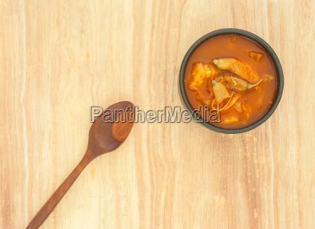 wuerzige saure suppe gemuese auf holzuntergrund
