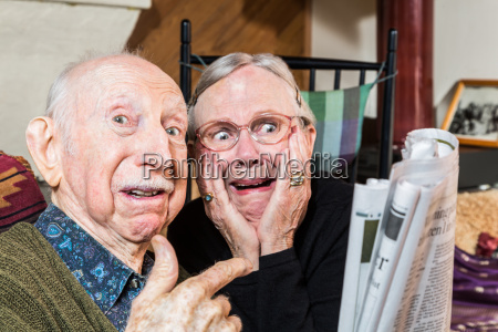 shocked older couple with newspaper