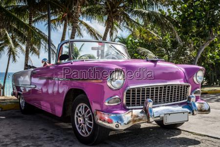 pinker amerikanischer cabriolet oldtimer parkt unter