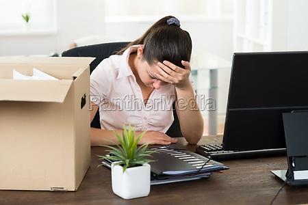upset geschaeftsfrau sitzung am schreibtisch