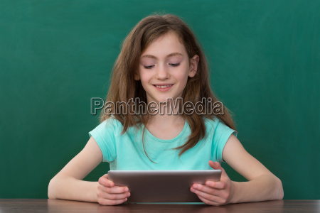 girl with digital tablet sitting at