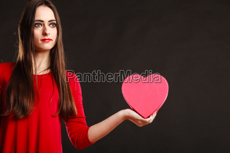 girl in red holding heart box