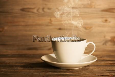 daempfender heisser kaffee in weissen tasse