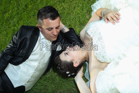 bride and groom resting on lawn