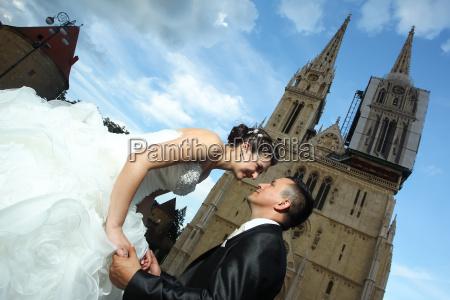 groom kneeling before bride in city