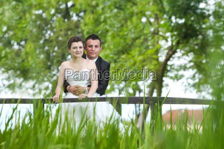married couple posing on wooden bridge
