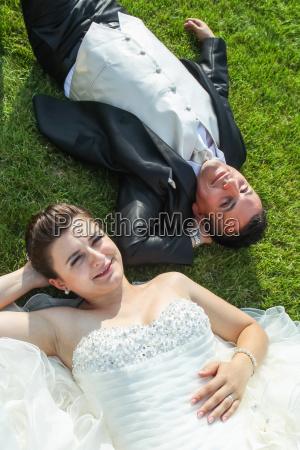 newlyweds resting on grass