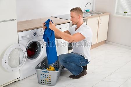 mann mit t shirt mit waschmaschine