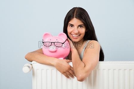 woman with piggybank and radiator