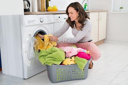 frau die kleidung in waschmaschine