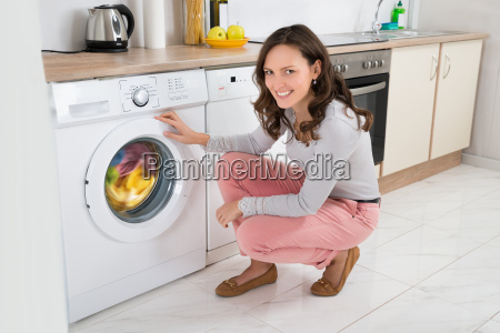 woman cleaning clothes in washing machine