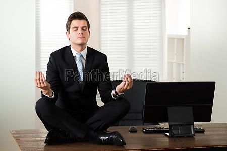 geschaeftsmann der meditation im buero