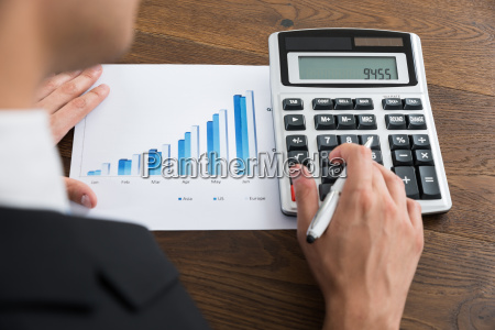 businessperson with graph and calculator at