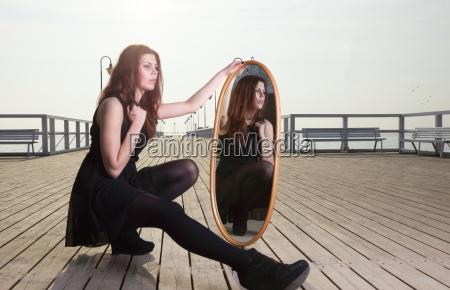 dachte frau schaut im spiegel an