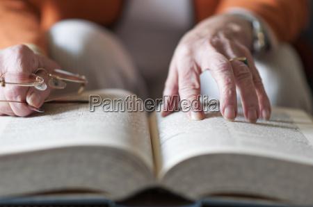 seniorin liest in einem buch
